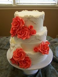 Coral Wedding - 8-, 10-, 12-inch round fondant with lace appliques and fondant ribbons. Ribbon and lace dusted with Super Pearl. Gumpaste roses