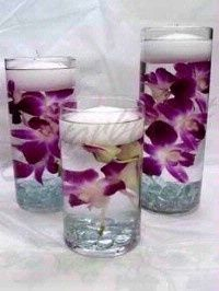 Centerpiece floating candles with flowers in water.