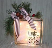 DIY Jingle all the way light box using glass blocks from the home improvement stores, diamond bit to cut hole, 35 strand clear lights, tinsel and decorations