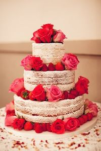 Un-iced wedding cake with red and pink roses + strawberries. Yum! #Celebstylewed #Naked.