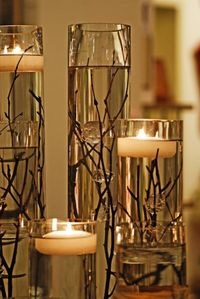 twigs in water with floating candle on top.--centerpieces