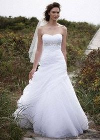 Delicate, graceful and airy, this elegant strapless organza wedding gown is ethereal. Ruching on bodice paired with dropped waist and draping detail on skirt results in the ultimate in figure flattery. Draped gown features intricate beading on empire wais...