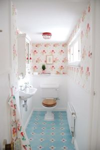 floral wallpaper; blue tiles on floor; this is cute; nice tiny sink!
